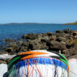 Holding the basket between my knees while I weave on the rocky beach, admiring the view out to sea