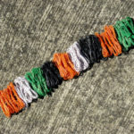 Coils of orange, white, green and black telephone wire laid out in a row on a concrete surface showing the intended pattern of colours for the Animals Asia basket