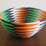 Side-on view of the completed Animals Asia basket in black, white, orange and green telephone wires in a chevron pattern
