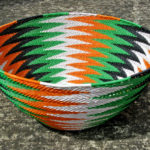 Telephone wire basket in a broad chevron pattern of orange, green, black and white wires on a concrete surface
