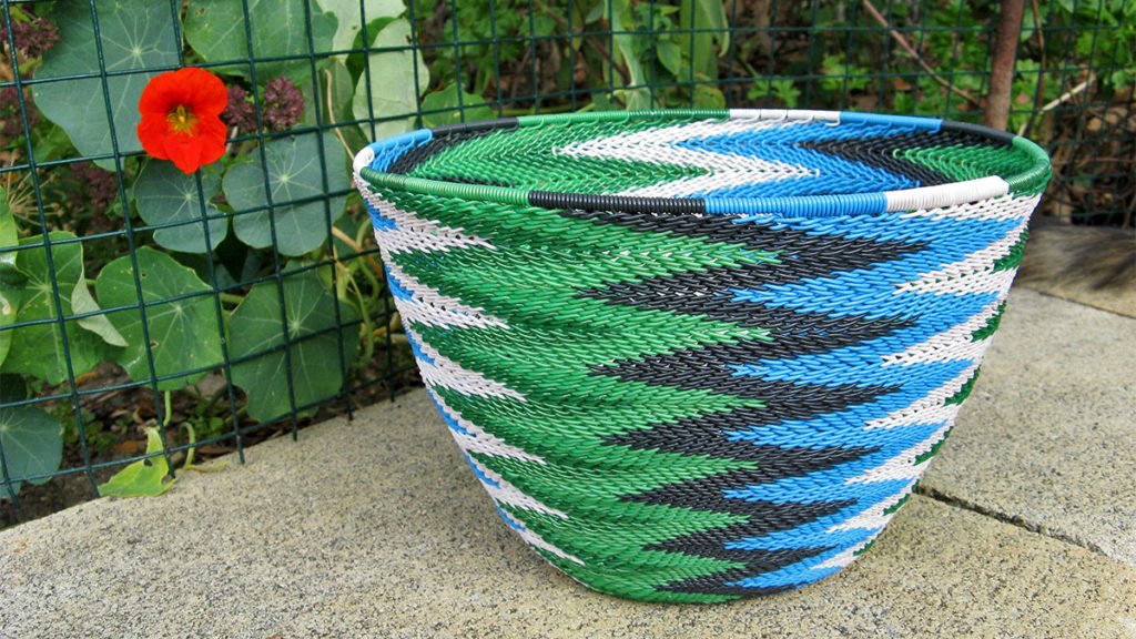 Telephone wire basket in a chevron pattern using bright blue, black, white, light green and dark green wires.