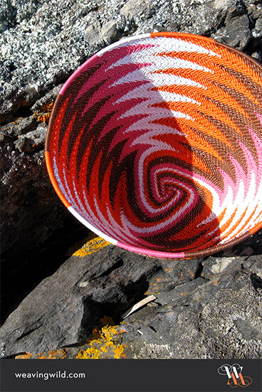 Chevron-patterned telephone-wire basket on lichen-covered coastal rocks at Penneshaw, Kangaroo Island.
