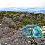 Telephone-wire basket on lichen-covered rocks on Mt Wellington, Tasmania, with the Derwent Estuary in the background.