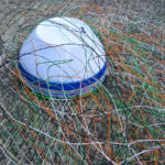 Close-up of a telephone wire basket with wires coiled around the frame and affixed to a mould, ready to start weaving