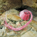Red and white wire basket in progress, nestled on a weathered sandstone rock face.