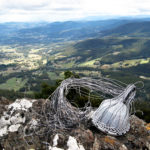 Telephone wire basket in progress, on lichen-encrusted boulders on Mt Montague, looking down onto the Mountain River settlement in southern Tasmania.