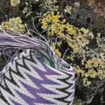 Purple, black and white telephone wire basket being woven in a chevron pattern, placed on a rock covered in a lemony lichen, Cameronia pertusarioudes.