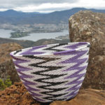 Sally's completed chevron-patterned basket on Mt Direction, with the Mt Wellington range and the northern suburbs of Hobart in the background.