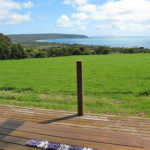 A row of telephone wire coils on a wooden deck table, with a lush green paddock and Antechamber Bay in the background.