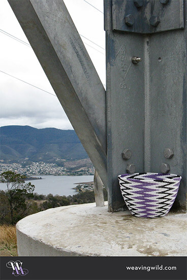 Chevron-patterned basket on Mt Direction, with the Mt Wellington range and the northern suburbs of Hobart in the background.