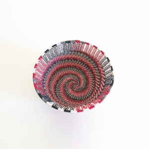 Top view showing the inside base of a small red, black, grey and white telephone wire basket