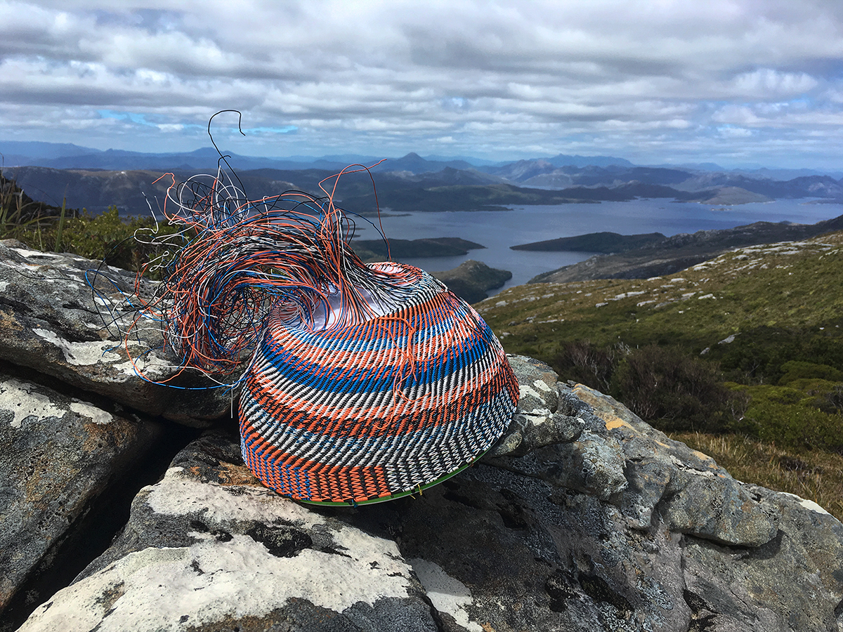 A wire basket in progress on a large boulder with the Lake Pedder impoundment in the distance.