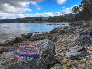 Telephone wire basket in progress on a stony beach near Cygnet, Tasmania, with two cormorants in the background.